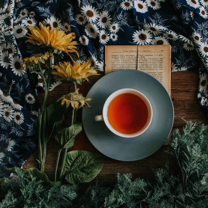 mug of tea sitting on book surrounded by yellow flowers